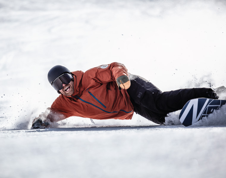 A snowboarder lays a deep toeside turn