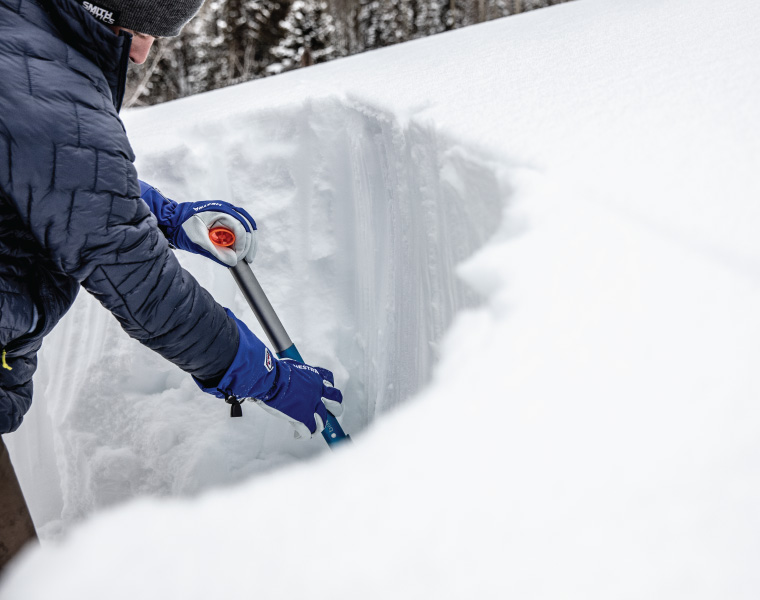 A skier digs a snow pit in Hestra gloves